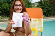 Girl in glasses sits open legged by the pool.